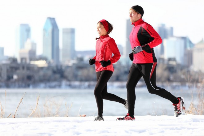 Runners running in winter snow with city skyline background. Healthy multiracial young couple. Asian woman runner and Caucasian man running with Montreal skyline, Quebec, Canada